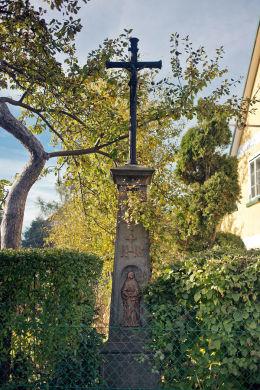 Krzyż przydrożny metalowy na kamiennym postumencie stojący przy ulicy Polnej. Chełmsko Śląskie, gmina Lubawka, powiat kamiennogorski.