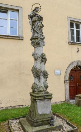 Barokowa kolumna Matki Boskiej przed budynkiem plebanii parafii pw. Wniebowzięcia Najświętszej Marii Panny i św. Maternusa. Lubomierz, powiat lwówecki.