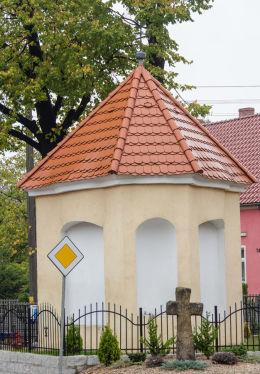 Krzyż pokutny stojący obok przydrożnej kapliczki domkowa. Lutomia Dolna, gmina Świdnica, powiat świdnicki.