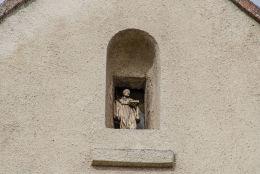 Kapliczka gablowa z figurą świętą w szczycie budynku przy ulicy Kościelnej. Wierzbna, gmina Żarów, powiat świdnicki.