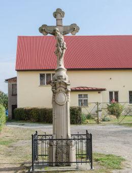 Przydrożny krzyż kamienny stojący na przeciw kościóła p.w. Św. Wawrzyńca. Budzów, gmina Stoszowice, powiat ząbkowicki.