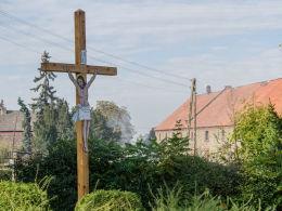 Drewniany krzyż przydrożny z blaszaną figurą Chrystusa. Mikołajów, gmina Stoszowice, powiat ząbkowicki.