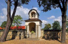 Kapliczka przy murze okalającego bazylikę św. Stanisława Biskupa. W górnej części figura św. Kingi. Szczepanów, powiat brzeski.