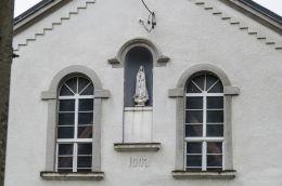 Kapliczka wnękowa Matki Boskiej z 1903 r w szczycie domu. Zakliczyn, powiat tarnowski.