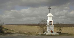 Krzyż przydrożny, metalowy na kamiennym postumencie, stojący przy drodze Białobrzegi - Mogielnica. Pacew, gmina Promna, powiat białobrzeski.