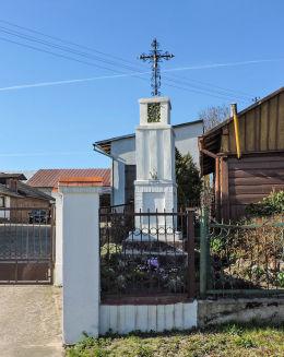 Krzyż przydrożny metalowy na kamiennym postumencie. Dębnowola, gmina Mogielnica, powiat grójecki.