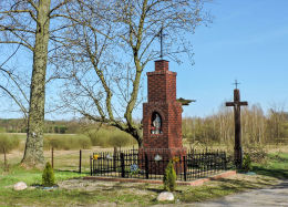Krzyż przydrożny metalowy na murowanym postumencie. Obok krzyż drewniany. Dziarnów, gmina Mogielnica, powiat grójecki.