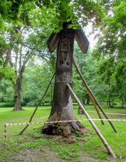 Przydrożna kapliczka z Chrystusem Frasobliwym z pnia drzewa w parku pałacowym. Warka, powiat grójecki.