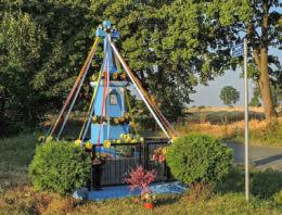 Przydrożny krzyż kamienny z 1909 r. stojący na skraju wsi. Ruda Mała, gmina Kowala, powiat radomski.
