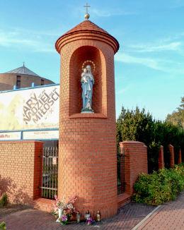Przydrożna kapliczka Matki Boskiej w murze otaczającym kościół Zesłania Ducha Świętego. Warszawa, Bielany.