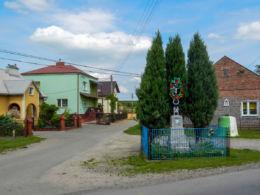 Krzyż przydrożny metalowy na kamiennym postumencie. Ostrów, gmina Radymno, powiat jarosławski.