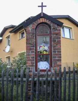 Przydrożna kapliczka stojąca na skrzyżowaniu ulicy Piastowskiej z Modrzańską. Orzesze, Woszczyc, powiat mikołowski.
