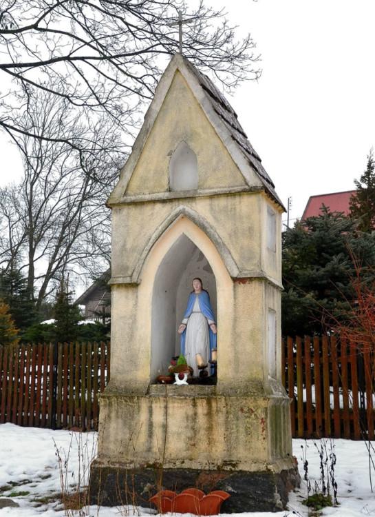 Przydrożna kapliczka maryjna, z dwuspadowym daszkiem, zwieńczonym krzyżem. Wilimy, gmina Biskupiec, powiat olsztyński.