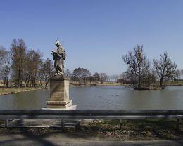 Przydrożna kapliczka murowana św.Jana Nepomucena stojąca nad brzegiem stawu przy drodze w kierunku Lubasza (po renowacji). Sławno gmina Lubasz, czarnkowsko-trzcianecki.