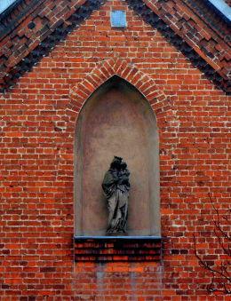 Figura Matki Boskiej z Dzieciątkiem w niszy w murze kaplicy kościoła św. Mateusza. Opalenica, powiat nowotomyski.