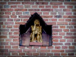 Kapliczka wnękowa z drewnianą rzeźbą Chrystusa Frasobliwego w murze kościoła św. Mikołaja. Mosina, powiat poznanski.