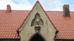 Figura św. Józefa w szczycie budynku dawnego szpitala pod jego wezwaniem. Wronki, powiat szamotulski.