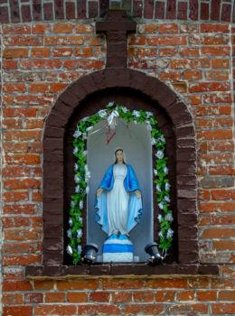 Kapliczka wnękowa z figurą Matki Boskiej na ścianie dawnej szkoły. Boruja, gmina Siedlec, powiat wolsztyński.