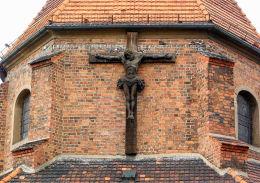 """Krzyż z ukrzyżowanym Chrystusem w szczycie kościoła farnego z napisem """"Boże błogosław Wrześni i Ojczyźnie naszej"""". Września, powiat wrzesiński."""