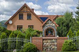 Kapliczka przydrożna, nowoczesna ulokowana w murze ogradzającym dom prywatny. Jaźwina, gmina Łagiewniki, powiat dzierżoniowski.
