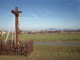 Krzyż przdrożny, drewniany w tle przedmieścia Świdnicy i Sobótka. Komorów, gmina Świdnica, powiat świdnicki.