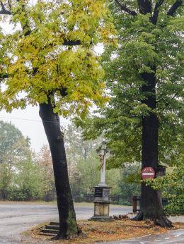 Przydrożny krzyż kamienny na skwerze w pobliżu kościoła Przemienienia Pańskiego. Lutomia Dolna, gmina Świdnica, powiat świdnicki.