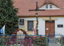 Drewniany krzyż przydrożny przed budynkiem parafii. Olszany, gmina Strzegom, powiat świdnicki.