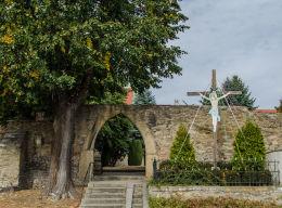 Przydrożny krzyż drewniany stojący obok kościoła Wniebowstąpienia NMP. Wierzbna, gmina Żarów, powiat świdnicki.