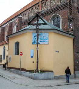 Krzyż z ukrzyżowanym Chrystusem w narożniku Rynku. Kożuchów, powiat nowosolski.