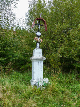 Krzyż przydrożny metalowy na kamiennym postumencie. Szczawnik, gmina Muszyna, powiat nowosądecki.