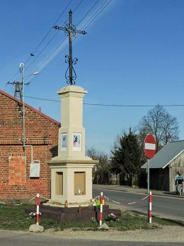 Krzyż przydrożny, metalowy na kamiennym postumencie stojący u zbiegu ulicy Kościelnej i Władysława Rosłońca. Przybyszew, gmina Promna, powiat białobrzeski.