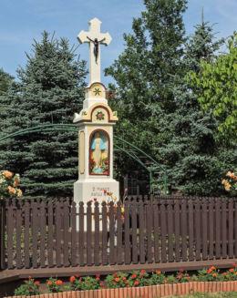 Przydrożny krzyż z kapliczką stojący w centrum wsi. Różanna, gmina Odrzywół, powiat przysuski.