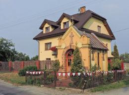 Kapliczka przydrożna przy drodze Ludwinów - Sołtyków, za nią budynek mieszkalny Trablice 91a. Trablice, gmina Kowala, powiat radomski.