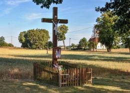 Krzyż przydrożny drewniany z kapliczką. Komorzno, gmina Wołczyn, powiat kluczborski.