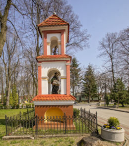 Przydrożna kapliczka z figurą św. Jana Nepomucena stojąca przed kościołem pw. św. Jana Chrzciciela i św. Barbary. Ulanów, powiat niżański.