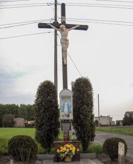 Krzyż przydrożny z kapliczką. Ufundowany w 1934 roku przez  F. i K. Kaniewskich po wygranej sprawie sądowej o pole. Bełk, gmina Czerwionka Leszczyny, powiat rybnicki.