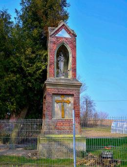 Kapliczka murowana wzniesiona w 1908 roku. We wnęce znajduje się figura Matki Boskiej z Dzieciątkiem. Szczęsne, gmina Purda, powiat olsztyński.