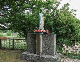 Kapliczka z figurą Matki Boskiej obok kościoła na postumencie pomnika pierwszowojennego. Drzonowo Wałeckie, gmina Człopa, powiat wałecki.