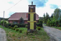 Przydrożna kapliczka słupowa stojącya na rozstaju dróg. Strzaliny, gmina Tuczno, powiat wałecki.